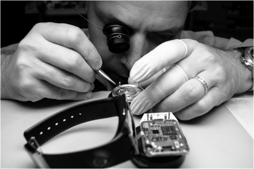 Watchmaker inspecting watch movement